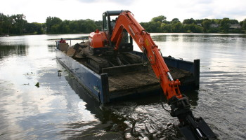 Accessing a lakefront retaining wall using a barge